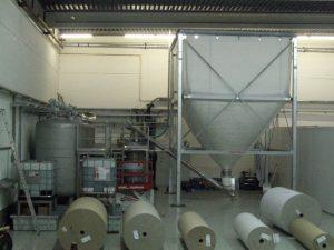 """Textilsilo in einem Produktionsgebäude. Der Auslass der Silos endet in einer Förderschnecke. Auf dem Rahmen des Silos steht """"CAVITRON"""""""