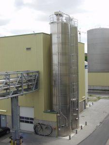 Zwei Aluminiumsilos, die seitlich an einem Produktionsgebäude abgestützt werden.