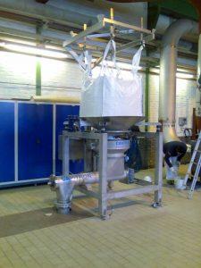 Installierte Big-Bag Entleerstation in einem Produktionsraum. Sie besteht aus: Höhenverstellbares Trägergestell, Big-Bag, Klemmbrille, Zwischenbehälter, Förderschnecke.