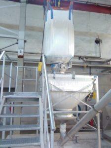 Ein weißes Big-Bag hängt an einem Krangestell. Der Auslass ist über eine Klemmbrille mit einem weißen Zwischenbehälter aus Textil verbunden. Der Auslass des Zwischenbehälters führt zu einer Förderschnecke