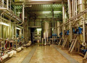 Produktionshalle mit Anlage links, rechts und hinten. Links sind Pumpen zu sehen, hinten stehen Vorratsbehälter und rechs sind die Haltestrecken der Kocheranlage zu sehen.