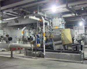 Die Gummilöseanlage steht in der Mitte vom Bild. Gut zu sehen ist der Antriebsstrang der Förderschnecke leicht rechts im Bild. Um die Anlage herum ist eine Industrieumgebung zu sehen.