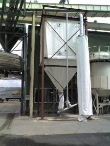 ein weißes, quadratisches Textilsilo mit rundem Auslass unten. Es hängt in einem roten Rahmen und steht vor einem Produktionsgebäude.