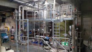 Eine enzymatische Stärkeleimaufbereitungsanlage im Produktionsgebäude. Um die Anlage herum sind Plattformen zum Erreichen des Behälterdeckels angebracht.