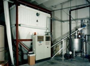 a textil silo hanging in a red frame. In front of it is a switch cabinet. On the right you can see a conveyor screw connected to a preparation tank.