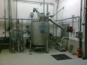In the center there is a conical preparation tank. On top of it is a conveyor screw. Some pumps and pipes are located right and left of the plant.The plant is located in a white room.
