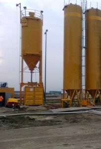 one small and two bigger, yellow silos on a construction site. The smaller one has a yellow container underneath it.